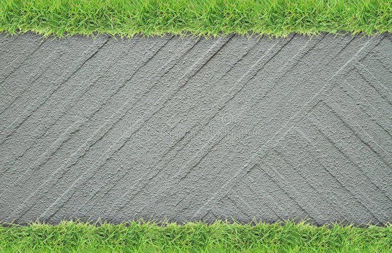 Green grass border on cement wall background. Green grass border on rough cement wall background royalty free stock image