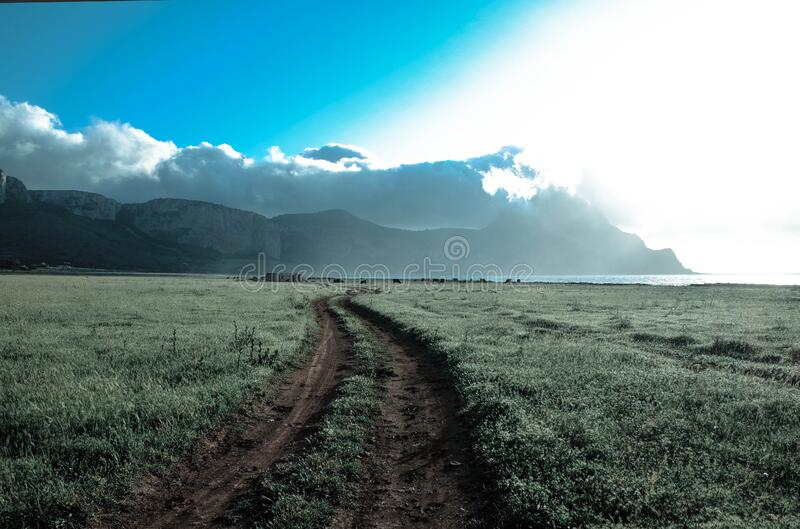 Green Grass Field Beside Brown Mountains Under White Cloudy Sky stock image
