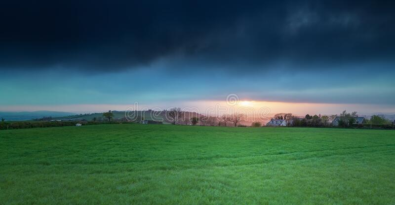 Green grass  field and a dramatic sky on sunset. In  south west of Ireland in spring royalty free stock photography