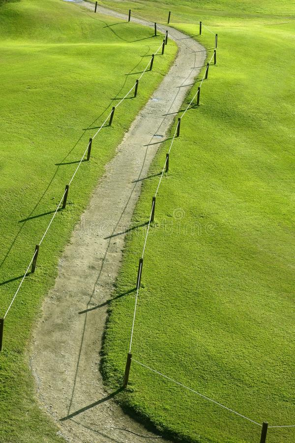 Green grass field meadow with winding road stock photo
