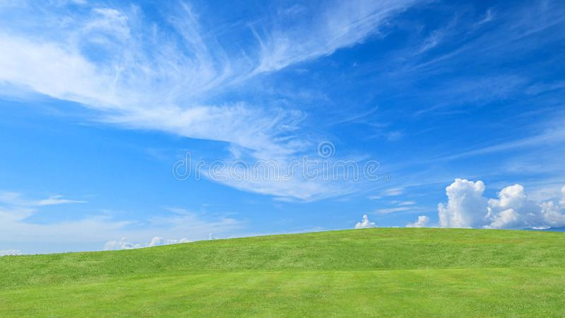 Green grass field on small hills and blue sky with clouds for background royalty free stock photography