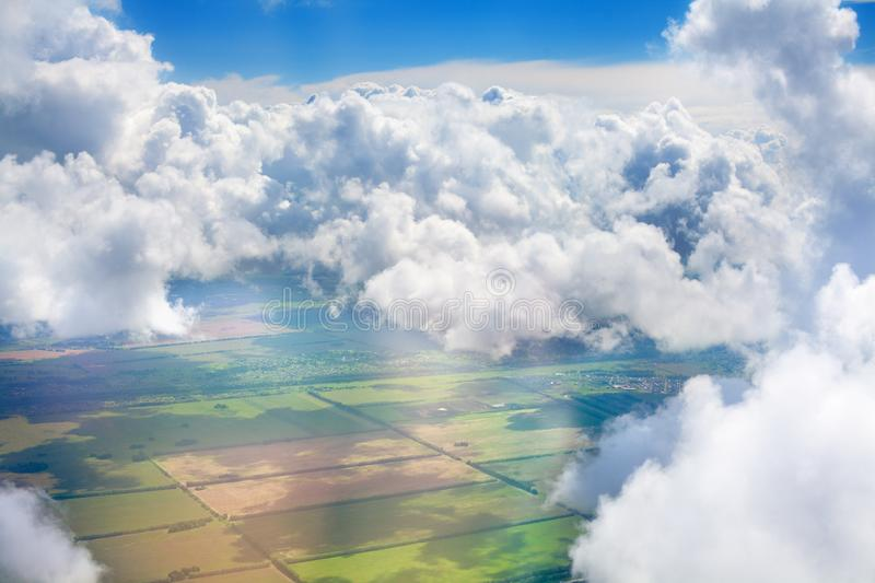 Green grass fields, forests, blue sky and white cumulus fluffy clouds background panoramic aerial view, sunny summer landscape stock photos
