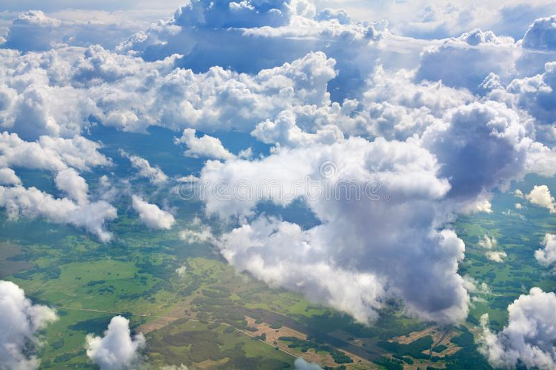 Green grass fields, forests, blue sky and white cumulus fluffy clouds background panoramic aerial view, sunny summer landscape royalty free stock photo