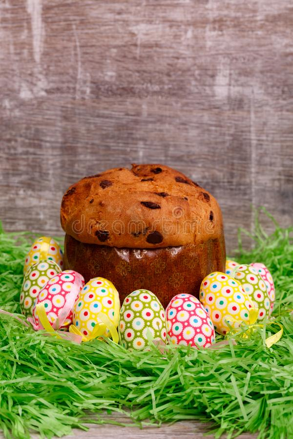 Green grass in front of a wooden background. Easter cakes and colorful eggs. Happy holidays royalty free stock photography