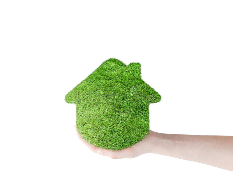 Green grass home icon in his hand. Abstract green grass house on over white background. Ecology concept royalty free stock photography