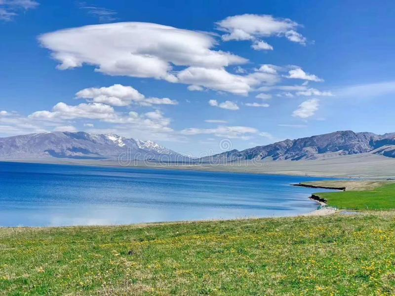 Clear water, blue sky, grassland, mountain range, like a painting royalty free stock images