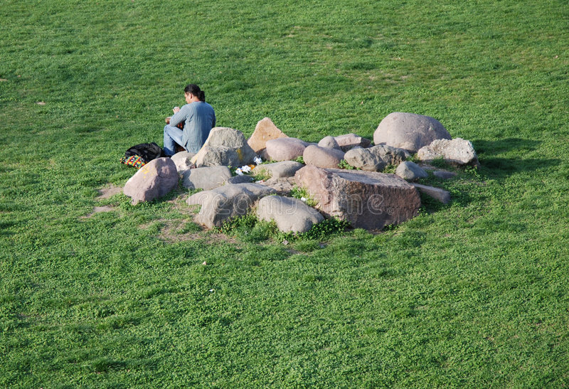 Green grass, rocks and men. Natural grass rocks and men - illuminated by the sun, green grass, fresh grass, grass for background, uncut grass, grass in italy royalty free stock photography