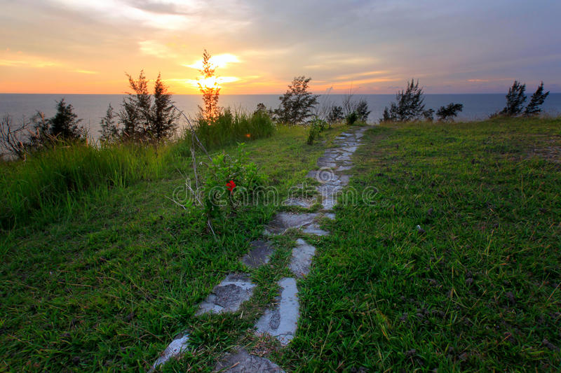 Green grass and stone path with sunset