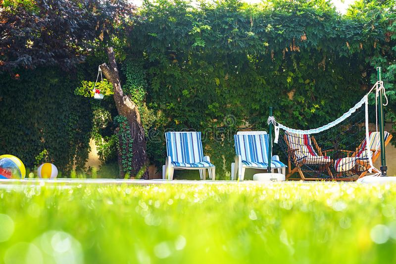 Green grass with water drops and green bokeh background on the yard with swimming pool and deck chairs for friends at garden party royalty free stock image