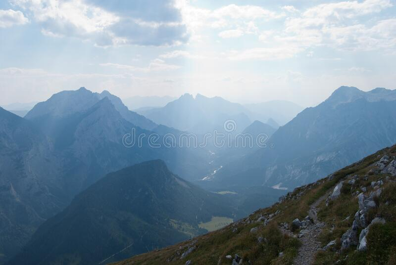 Green Grasses on Rocky Mountains Under Blue Sky stock photography