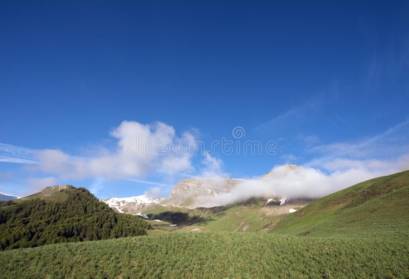 Green grassy hills under snow capped mountains of haute provence near col de vars in france. Green grassy hills under snow capped mountains of haute provence royalty free stock image