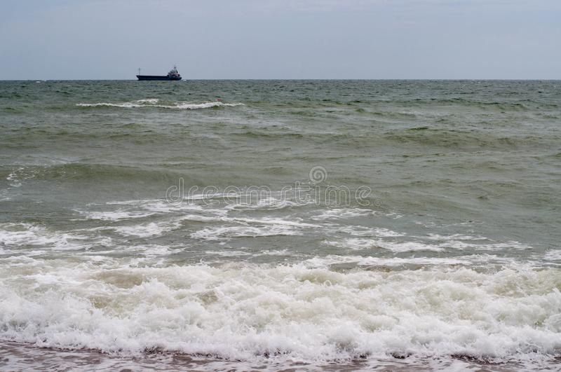 Green grey water of stormy seascape with white sea foam. On surf wave at wet beach sand. Blurred dark vessel silhouette on skyline with blue cloudy sky. Storm royalty free stock image