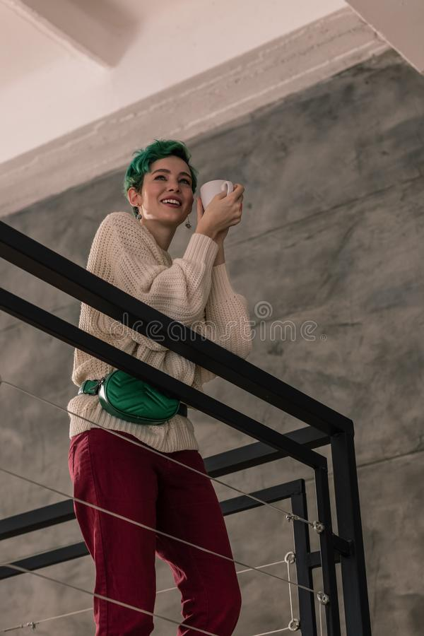 Green-haired woman wearing dark red trousers drinking tea. Dark red trousers. Green-haired stylish young woman wearing dark red trousers drinking tea royalty free stock photography