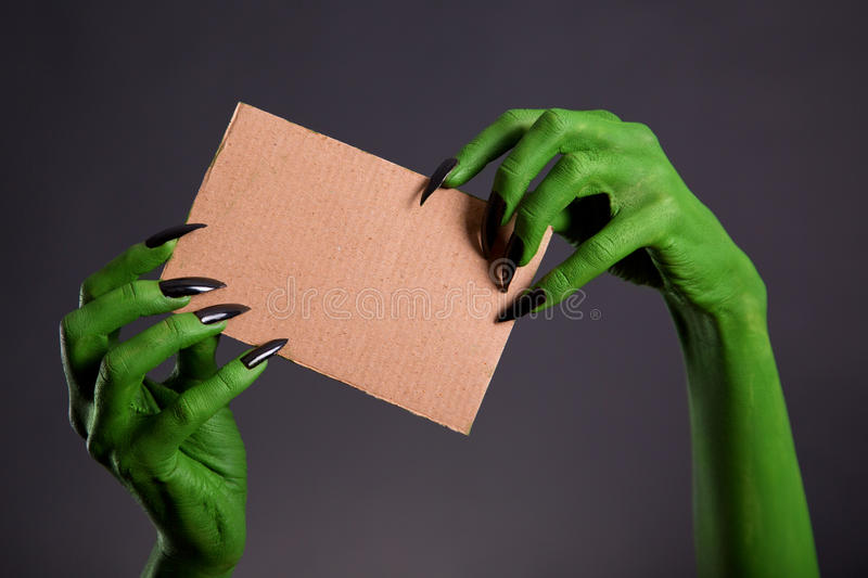 Green hands with long black nails holding empty piece of cardboa. Rd, Halloween theme stock photo