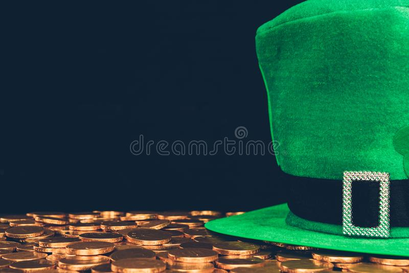 Green hat on golden coins isolated on black, st patricks day concept royalty free stock photo
