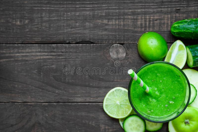 Green healthy smoothie in a glass with spinach, apple, cucumber and lime with a straw over rustic wooden table. Top view with copy space. detox drink stock photos