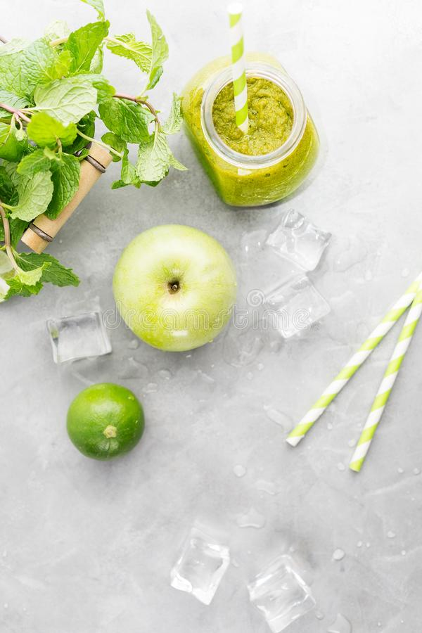 Green healty drink in mason jar with green apple, mint, lime and melting ice cubes on grey background. Vegetarian food concept. De royalty free stock images
