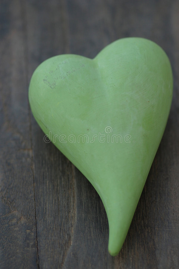 Green heart. On dark wood stock photos