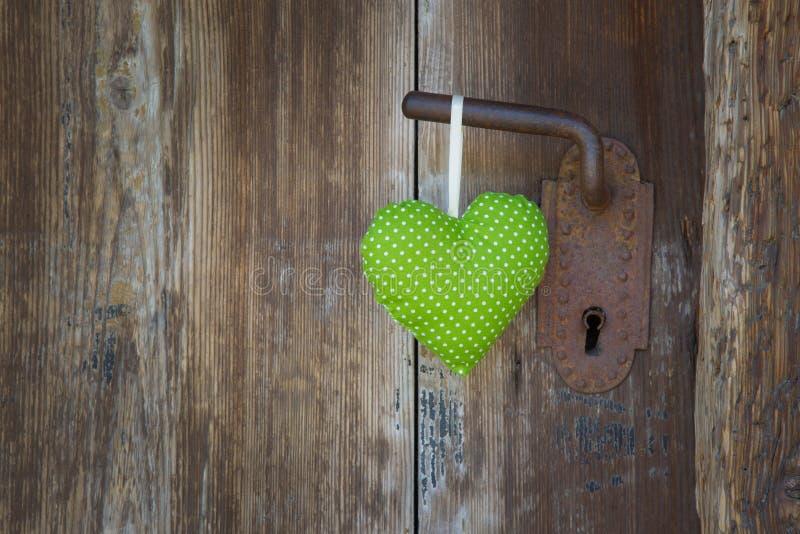 Green heart shape hanging on door handle - wooden background wit stock photography