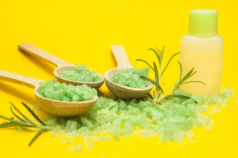 Green herbal salt, rosemary and bottle of essential oil on a yellow background royalty free stock image