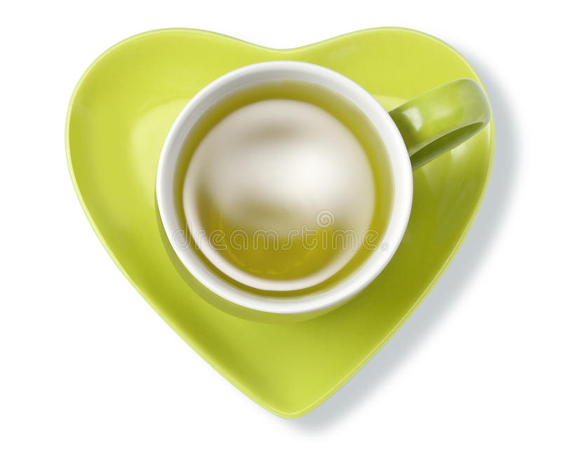 Green Herbal Tea Cup Heart Health. A cup of green herbal tea with a heart shape saucer isolated on white shot from above royalty free stock photos