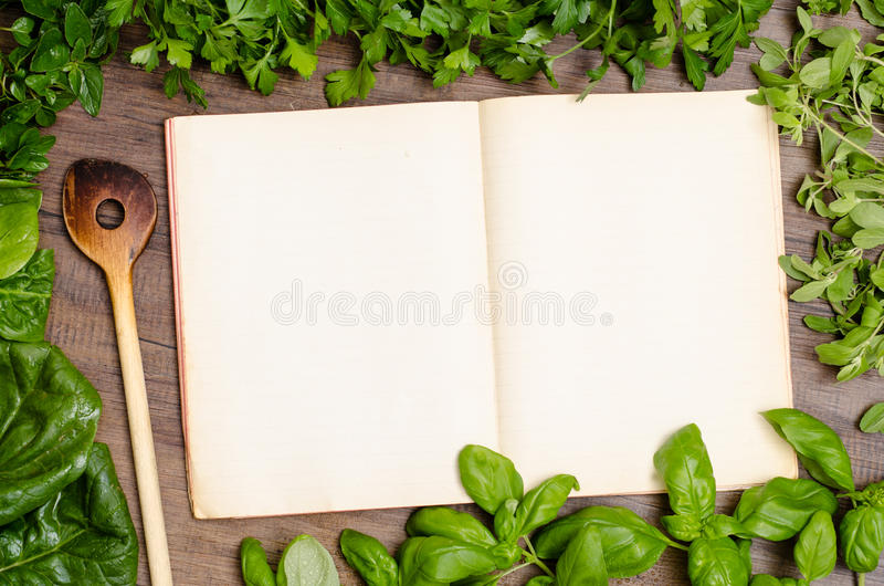 Green herbs as frame around a cookbook. For recipes royalty free stock photography