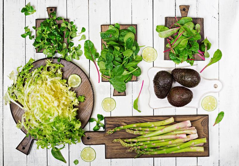 Green herbs, asparagus and black avocado on a white wooden background. Top view. stock images