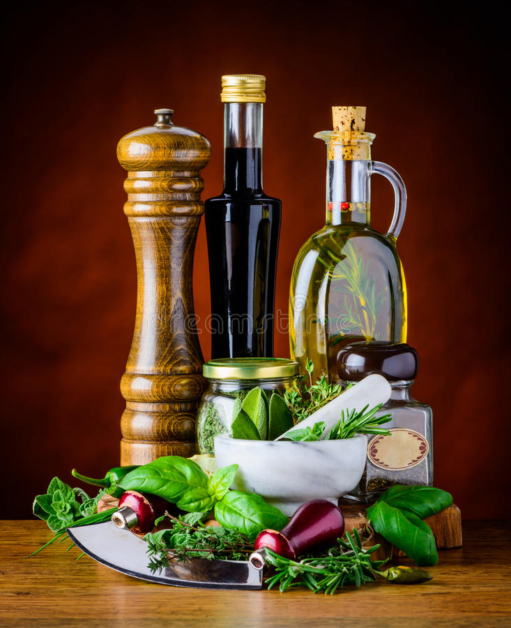 Green Herbs, Food Seasoning and Olive Oil. Green Basil and Sage with herbs chopper and bottles of Balsamic vinegar with virgin olive oil royalty free stock image
