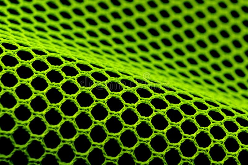 Mesh. Green hexagonal textile mesh on black background