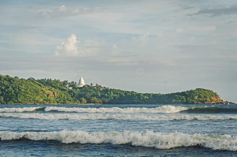 Green hill with Buddha temple stock photo