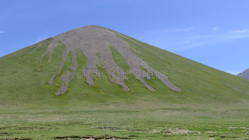 Green hill with a palmated, barren and rocky summit on Tibetan Plateau. Qinghai, China royalty free stock photos