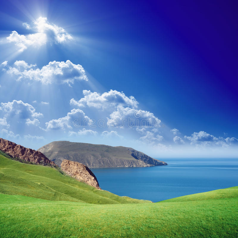 Green hills, blue sea and sky. Beautiful nature background - green grass hills, mountains, blue sky, island in sea, bright sun in white clouds stock image