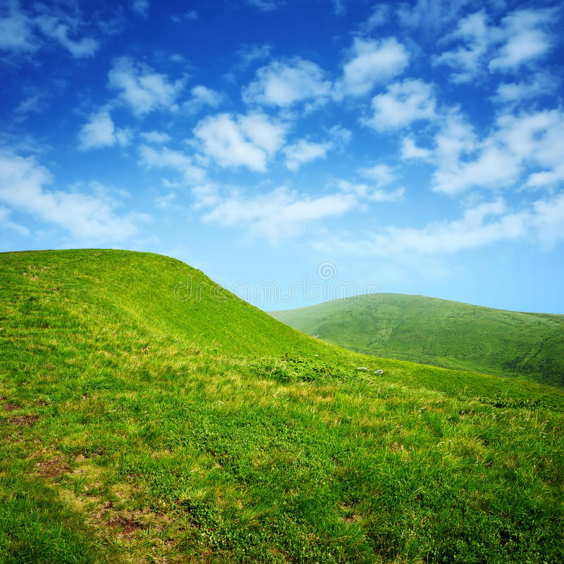 Green hills and blue sky with clouds royalty free stock photography