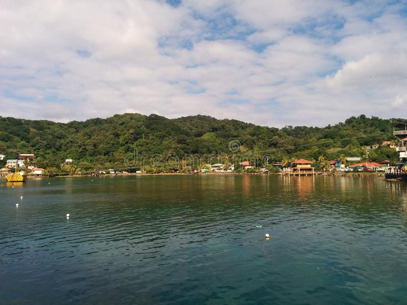 Green hills on island shore with cloudy blue sky and sea. Green hills and buildings on island shore with cloudy blue sky and sea in Roatan, Honduras stock image