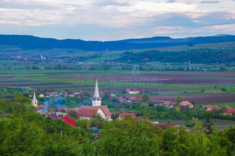 Green hills in a mountain valley. Summer landscape. At the foot of the mountains is a small village with small houses.  stock photos