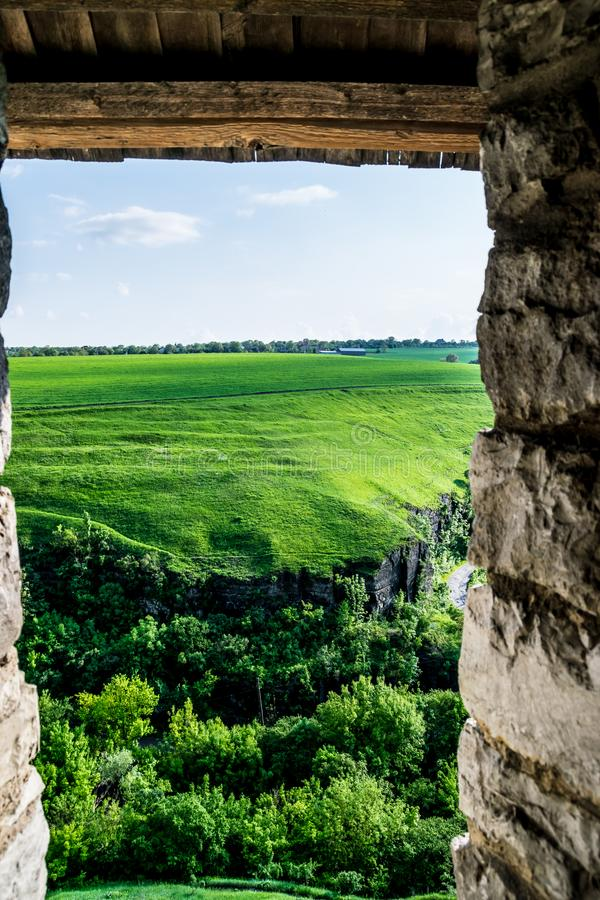 Green hills under fortress walls. Top down view to the country landscape from loophole in fortifications of Kamianets-Podilskyi Castle in Ukraine. A riot of stock images