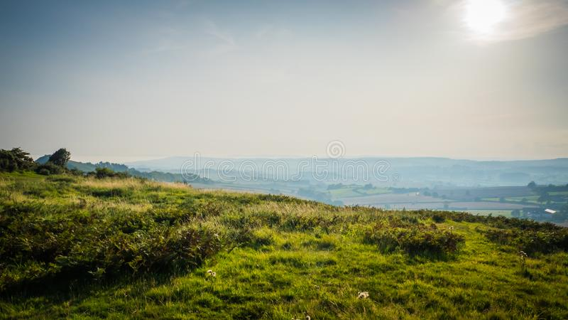 Green hilly countryside in Devon, United Kingdom. Green hilly with orange cliffs landscape on Jurassic coast near Sidmouth, Devon, in the United Kingdom, UK royalty free stock images