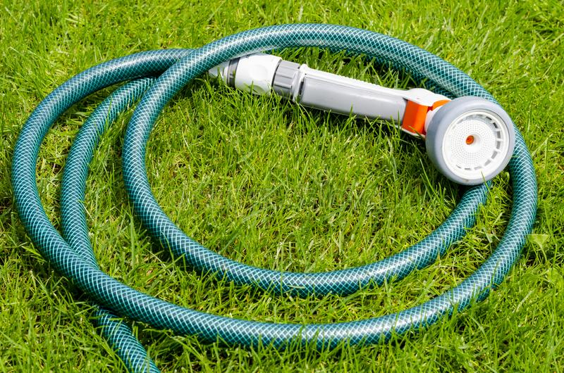 Green hose for watering lies on grass, lawn. Studio Photo stock photography