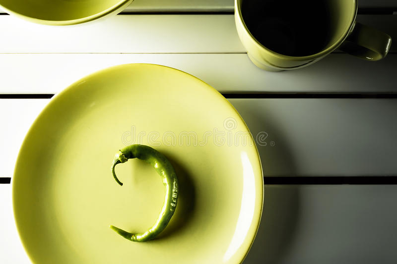Green hot pepper on dish. Top view green hot pepper on green dish over white wood. Horizontal image stock photo