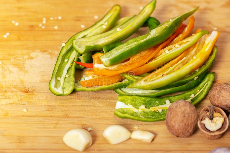 Green hot pepper with garlic and nuts. On a wooden board stock photos