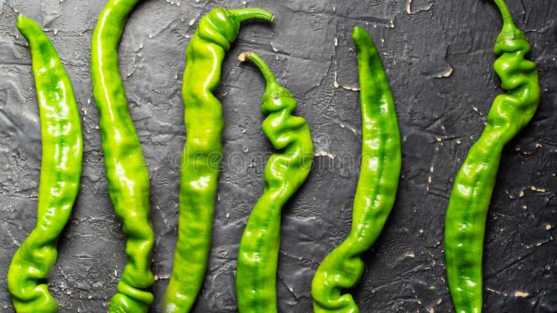 Green hot pepper pods on a black textured background. Row of green chili pepper pods on a black textured background stock photos