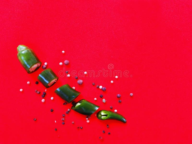 Green hot pepper on red plain background. Green hot pepper on red uniform background royalty free stock photography