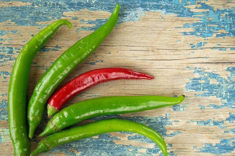 Green hot pepper on rustic wooden background. Culinary background. Top view with copy space stock photos