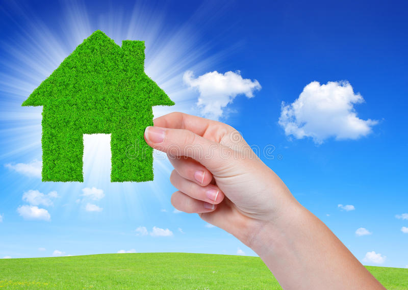 Green house in hand. On blue sky stock photos