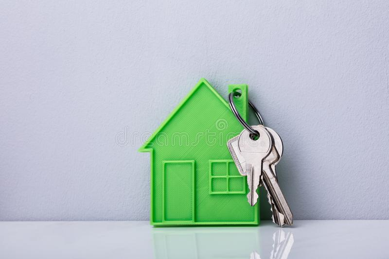 Green House Keychain With Keys. Close- Up Of A Green House Keychain Against White Wall stock photo