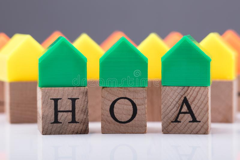 Close-up Of House Model Over Wooden Block. Green House Model Over Homeowner Association Wooden Blocks royalty free stock image