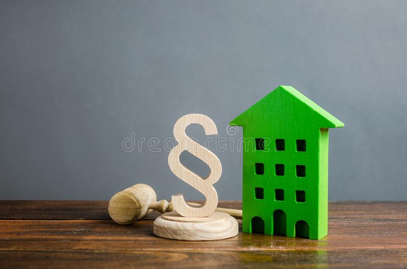 Green house and paragraph figurine with a judge gavel. Concept legislation on residential buildings and infrastructure. royalty free stock image