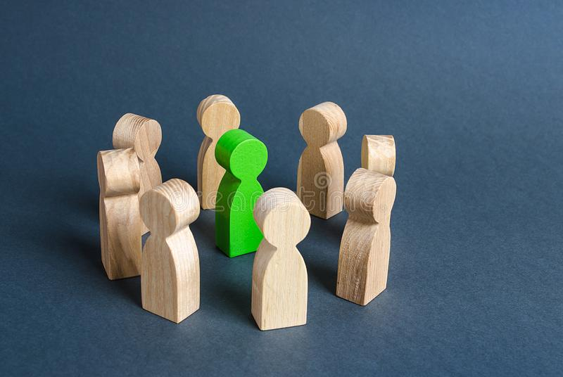 A green human figure is surrounded by a circle of people. Cooperation and collaboration. Fundraising and people around the idea. To unite like-minded persons royalty free stock photo