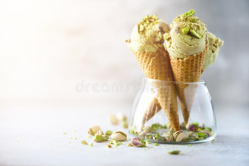 Green ice cream in waffle cone with chocolate and pistachio nuts on grey stone background. Summer food concept, copy royalty free stock photos