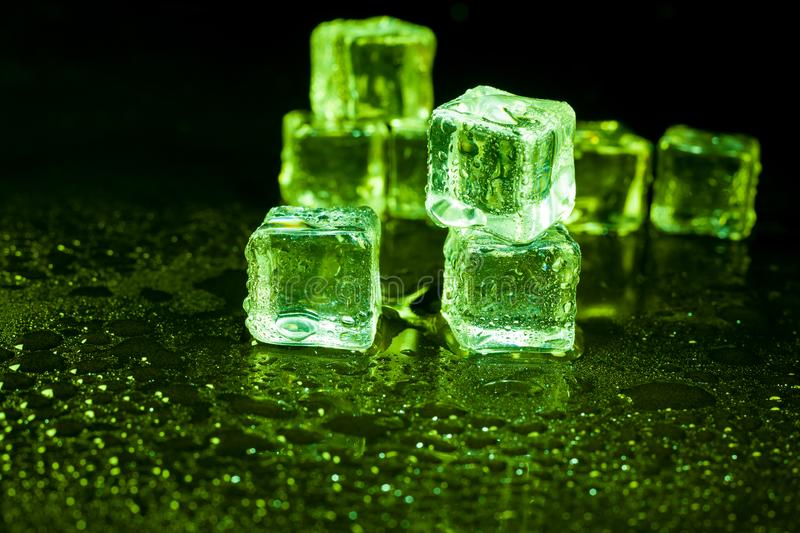 Green ice cubes on black background stock photography